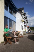 A man reading some tourism literature and enjoying a coffee at cafe on the main road through the village of Arisaig, Highlands of Scotland. Iain McLean / Scottish Viewpoint horizontal,day,summer,sunny,sunshine,blue,sky,skies,Arisaig,Lochaber,village,shop,shops,cafe,people,person,retail,shopping,one,man,40-60,years,street,road,rhu,drink,drinking,coffee,enjoy,enjoying,tour