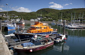 The RNLI Lifeboat moored at the busy port of Mallaig, Highlands of Scotland. Iain McLean / Scottish Viewpoint horizontal,day,summer,sunny,sunshine,blue,sky,skies,Mallaig,Lochaber,village,coast,coastal,Scotland,Scottish,UK,U.K,Great,Britain,no people,nobody,busy,port,harbour,boats,fishing,water,marina,activity