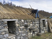 A man thatching the roof of a traditional blackhouse croft at the Highland Folk Museum, Newtonmore, Highlands of Scotland. Doug Houghton / Scottish Viewpoi horizontalal,outdoors,outside,summer,sunny,blackhouse,black,house,thatching,roof,thatched,cottage,croft,Highland Folk Museum,one man only,1 person,50-60 years,traditional,Newtonmore,Highlands,thatch,h