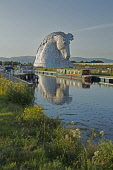 The Kelpies by sculptor Andy Scott, reflected in the Forth and Clyde Canal, part of The Helix - a land transformation project in the Falkirk District. Scotland Dennis Barnes / Scottish Viewpoi Summer,sunny,sunshine,water,Kelpies,sculpture,Andy Scott,Forth,Clyde,Canal,Helix,land,transformation,project,Falkirk,public,art,Scotland,Scottish,UK,U.K,Great Britain,outdoors,daytime,group,canalboats