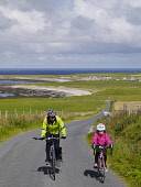 Cycling along the coast road to Birsay on Orkney's  West Mainland, Scotland. Mark Ferguson/ Scottish Viewpoin mother,daughter,cycling,hill,outdoor,sunny,Orkney,Scotland,Birsay,uphill,road,single track,8 year old,female,child,woman,exercise,activity,active,fit,UK,family,cycle,bike