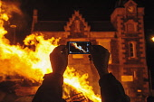 A person photographs the bonfire using their mobile phone the bonfire during the Hogmanay celebrations in the town centre of Biggar, South Lanarkshire, Scotland. Andrew Wilson / Scottish Viewpoi horizontal,outdoors,outside,winter,night,dark,Biggar,South Lanarkshire,Hogmanay,New Year,New Years Eve,event,fire,celebrate,tradition,celebration,ritual,heat,flames,burn,burning,1 person,one,mobile ph