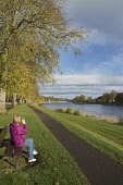 A woman sitting by the River Ness takes a photograph with the camera on her mobile phone, with a view towards the city centre of Inverness where the cathedral and the castle are visible, Highlands of... Dennis Barnes / Scottish Viewpoi vertical,outside,outdoors,day,autumn,autumnal,sunny,sunshine,blue sky,River Ness,Inverness,Scotland,Scottish,UK,U.K,United Kingdom,one woman only,1 person,60-70 years,elderly,fallen leaves,walker,walk