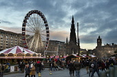 The Christmas Market on the Mound with the Big Wheel and Scott Monument visible behind - part of Edinburgh's Christmas, in the city centre of Edinburgh. Dennis Barnes / Scottish Viewpoi horizontal,outside,outdoors,afternoon,dusk,winter,Christmas Market,The Mound,Edinburghs Christmas,city,Edinburgh,Scotland,Scottish,UK,U.K,Great Britain,people,crowd,xmas,stalls,big wheel,fairground,Sc