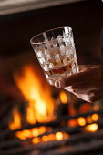Savouring a glass of whisky by the fire, Scotland. John Paul / Scottish Viewpoint vertical,inside,indoors,interior,evening,night,Scotland,Scottish,UK,U.K,Great Britain,one man only,1 person,fire,fireside,warm,warming,single malt,whisky,drink,drinking,glass,savouring,enjoying,dram