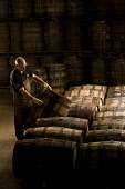 A worker with whisky barrels in  Glenfiddich distillery - a Speyside single malt Scotch whisky distillery in Dufftown, Moray, Scotland. John Paul / Scottish Viewpoint inside,interior,indoors,Glenfiddich Distillery,Dufftown,Moray,Scotland,Scottish,UK,U.K,Great Britain,1 person,one man only,45- 55 years,single malt,whisky,production,cask,barrels,worker,speyside