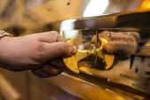 A distillery worker adjusts the Spirit Safe at the Glenmorangie Distillery - a Highland single malt Scotch whisky distillery, Tain, Highlands of Scotland. John Paul / Scottish Viewpoint horizontal,indoors,interior,inside,day,Glenmorangie Distillery,Tain,Highlands,Scotland,Scottish,UK,U.K,Great Britain,1 person,one man only,hand,single malt,spirit,whisky,stillroom,still,room,process,p