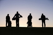 The silhouette of four golfers on the horizon walking with their clubs and golf trolleys at the Royal Dornoch Golf Club, Highlands of Scotland John Paul / Scottish Viewpoint uk,u.k,Great Britain,GB,G.B,Scotland,Scottish,day,Highlands,outdoors,summer,sunny,4 people,Royal Dornoch Golf Club,course,golf,golfing,club,golf trolleys,silhouette,golfers