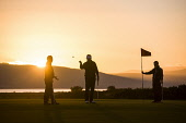 The silhouette of three golfers in late evening sunshine on the green at the Royal Dornoch Golf Club, Highlands of Scotland John Paul / Scottish Viewpoint uk,u.k,Great Britain,GB,G.B,Scotland,Scottish,day,Highlands,outdoors,summer,sunny,3 people,Royal Dornoch Golf Club,course,golf,golfing,club,striking,golfer,silhouette,flag,green