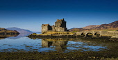 Eilean Donan Castle and Loch Duich at Dornie, Highlands of Scotland. Andrew Wilson / Scottish Viewpoi horizontal,outdoors,outside,day,winter,sunny,sunshine,blue sky,Loch Duich,Eilean Donan Castle,Highland,Scotland,Scottish,UK,U.K,Great Britain,nobody,water,panoramic,heritage,history,building,attractio