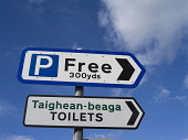 Signs for a free car park and the toilets photographed against a blue sky, Highlands of Scotland. Doug Houghton / Scottish Viewpoi horizontal,outdoors,outside,day,sunny,sunshine,sign,scotland,blue sky,skies,toilets,signpost,gaelic,signs,toilet,public,services,lavatories,signage,lavatory,arrow,direction,post,posts,signposts,nobody