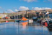 The lifeboat and fishing boats moored at the harbour at Girvan, South Ayrshire, Scotland. D.G.Farquhar / Scottish Viewpoin horizontal,outdoors,outside,day,winter,sunny,blue sky,skies,fishing boats,lifeboat,RNLI,moored,harbour,Girvan,South Ayrshire,industry,nobody,water,church,steeple,town,River Girvan,hills