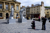 People take pictures of the miniature versions of The Kelpies by sculptor Andy Scott on display in The Square, Kelso, Scottish Borders Andrew Wilson/ Scottish Viewpoin Andy Scott,Kelpies,Sculptor,The Square,display,sculpture,Kelso,Scottish Borders,group,spring,tourists,tourist,people,attraction,attractions,visitor,visitors,temporary,touring exhibition,outdoors,dayti