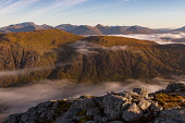 Morning light reaches over over the pass of Glencoe from Stob Coire Raineach as you see Ben Nevis in the far background. Highlands of Scotland Jason Baxter / Scottish Viewpoin Aonach Eagach,Highlands of Scotland,Glencoe,glen,coe,nobody,outdoors,daytime,uk,u.k,Great Britain,GB,G.B,Scotland,Scottish,Ben Nevis,atmospheric,mountain,mountains,hill,hills,munro,autumn,summer