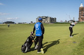 Golfer with caddie playing to 18th green on Old Course at St Andrews in Fife, Scotland, united Kingdom Iain Masterton / Scottish Viewpoint St Andrews,old,course,golf,Swilken,Burn,Bridge,golfer.caddie,golfing,fairway,18th,hole,links,view,travel,tourism,sport,heritage,landmark,historic,town,Fife,Scotland,Scottish,United,Kingdom,Britain,Bri