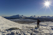 Female hill walker looking towards the snow covered Munros of (from left to right) Ben More, Stob Binnein, Cruach Ardrain, Beinn a' Chroin and An Caisteal from Ben Challum, winter, near Crianlarich, S... Richard Clarkson/ Scottish Viewpoint uk,u.k,Great Britain,GB,G.B,Scotland,Scottish,1 person,daytime,outdoors,female,woman,lady,hill,hills,mountain,mountains,walker,hillwalker,sun,winter,snow,cold,dramatic,rugged,wild,grandeur,Ben,Beinn,M