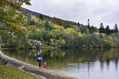 View of waterfront at village of Kenmore during autumn on Loch Tay in Perthshire , Scotland, United Kingdom. Iain Masterton/ Scottish Viewpoint Kenmore,Loch Tay,Perthshire,Scotland,Scottish,autumn,autumnal,colours,season,seasonal,seasons,villages,waterside,rural,travel tourism,UK,united Kingdom,Europe,European,2 people