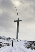 Man running in snow beside  wind turbine at Whitelee Windfarm in East Renfrewshire operated by Scottish power, Scotland, United Kingdom Iain Masterton/Scottish Viewpoint Whitelee Windfarm,wind farm,wind turbines,Whitelee Windfarm Scotland,renewables,renewable energy,wind turbine,investment,scottish windfarm,wind farms,windfarms,British wind farm,environment,runner,lei