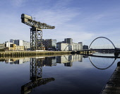 View of Finnieston Crane beside River Clyde on blue sky winter day, Scotland, United Kingdom Iain Masterton/Scottish Viewpoint Glasgow,River Clyde,riverside,Scotland,Scottish,city,Glasgow Finnieston Crane,cities,view,daytime,blue sky,reflection,reflections,Finnieston Crane,urban,regeneration,gentrification,redeveloped,develop