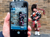 Tourist taking photo of Scottish man in tartan playing bagpipes on the Royal Mile in Edinburgh Old Town, Scotland, United Kingdom Iain Masterton/Scottish Viewpoint Edinburgh,Busker,tourism,tourists,playing bagpipes,man,tartan,Scotland,Scottish,Edinburgh Royal Mile,High Street,busking,traditional,Scottish culture,street scene,UK,United Kingdom,Britain,city,cities