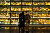Visitors looking at  bottles of Scotch Whisky on display at the Scotch Whisky Experience visitor centre on the Royal Mile in Edinburgh, Scotland, UK Iain Masterton /Scottish Viewpoint Scotch Whisky,Scotch Whisky Experience,Edinburgh,Royal Mile,Scotland,Scottish,bottles,collection,scotch whisky collection,interior,visitor centre,attraction,UK,United Kingdom,many bottles of scotch wh