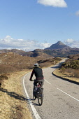 Cyclist on A894 North Coast 500 route near Laxford Bridge in Sutherland. Highlands of Scotland Mark Ferguson /Scottish Viewpoint uk,u.k,Great Britain,GB,G.B,Scotland,Scottish,1 person,daytime,outdoors,A894,north coast 500,cycling,cyclist,highland,sutherland,nc 500,road,highlands,ben stack,mountain,quiet,remote,sunny,blue sky,le