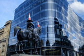 Old buildings reflected in a new glass fronted building in Queen Street, Glasgow, Scotland with the famous equestrian Wellington Statue in the foreground. Andrew Wilson /Scottish Viewpoint uk,u.k,Great Britain,GB,G.B,Scotland,Scottish,nobody,daytime,outdoors,Glasgow,Old,Queen Street,architecture,building,glass,man on horseback,new,reflections,traffic cone,wellington statue,cones