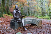 Statue of poet sits on outdoor Robert Burns on bench during autumn at the Birks O'Aberfeldy scenic area in Aberfeldy, Perthshire, Scotland,UK Iain Masterton /Scottish Viewpoint Birks O'Aberfeldy,robert burns statue,rabbie burns. scottish poet,Aberfeldy,Scotland,Scottish,outdoor,woodland,National Trust for Scotland,UK,United Kingdom,statue,sculpture,daytime,nobody,travel,tour