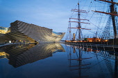 Exterior view of new V&A Museum and RRS Discovery ship at Discovery Point in the evening in Dundee, Scotland, UK. Architect Kengo Kuma. Iain Masterton /Scottish Viewpoint V&A Dundee,Dundee V&A,Dundee,V&A Museum,V&A Museum Dundee,Scotland,Scottish,new,modern,RRS Discovery,Discovery Point Dundee,architecture,building exterior,UK,united Kingdom,evening,illuminated,lit,dus