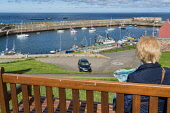 Dunbar harbour, boats, East Lothian,  Scotland, UK. Dennis Barnes /Scottish Viewpoint uk,u.k,Great Britain,GB,G.B,Scotland,Scottish,1 person,daytime,outdoors,Dunbar,harbour,boats,fishing,creels,East,Lothian,coast,coastal,coastline,water,sea,tourist,visitor,tourists