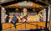 Edinburgh Christmas 2019: a stallholder in Princes Street Gardens waiting for customers  Editorial use only Andrew Wilson  /Scottish Viewpoint Christmas,Edinburgh's Christmas 2019,Xmas,entertainment,food,fun,fun fair,holiday season,princes street gardens,rides,shopping,stalls,street market,people