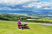 A woman at a picnic bench looking out to Howe of the Mearnes and Angus Glens from Hill of Garvock, Near Laurencekirk,  Aberdeenshire,Scotland UK Dennis Barnes /Scottish Viewpoint Howe,of,the,Mearns,and,Angus,Glens,from,Hill. of,Garvock,Near,Laurencekirk,historic,sunny,Aberdeenshire,Scottish,UK,United Kingdom,1 person,mountain,mountains,hill,hills,glen