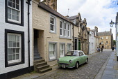 View along historic College Street with green car in central St Andrews, Fife, Scotland, UK Iain Masterton /Scottish Viewpoint St Andrews Scotland,St andrews,saint andrews scotland,st andrews fife,College Street St Andrews,Scotland,Scottish town,fife,Uk,United Kingdom,Britain,British town,scottish culture,Europe,travel,touris