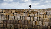 Solitary woman walking on harbour wall in St Andrews, Fife, Scotland, UK Iain Masterton /Scottish Viewpoint St Andrews Scotland,Scotland,St Andrews,Fife,Scottish town,harbour wall st Andrews,Uk,united kingdom,britain,british,sea wall,stone,blocks of stone wall,exterior,solitary woman,alone,single,female,wom