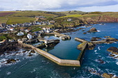Aerial view of small fishing village and harbour of St Abbs on North Sea coast in Scottish Borders, Scotland, UK Iain Masterton /Scottish Viewpoint St Abbs,St Abbs Scotland,Scotland St Abbs,fishing village,scottish fishing village,aerial,drone image,north sea coast,coastal community,UK,United kingdom,Britain British coast,daytime,view,travel,tour