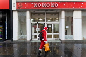 Man dressed as Santa Claus walks in front of closed down Christmas store called Ho Ho Ho on Argyll Street in Glasgow, Scotland ,UK Iain Masterton /Scottish Viewpoint Scotland,Scottish,Glasgow,lockdown,shops,shopping,city centre,stores,covid-19,coronavirus,pandemic,uk,united kingdom,britain,british,people,street,closures,father christmas,business,retail industry,tr